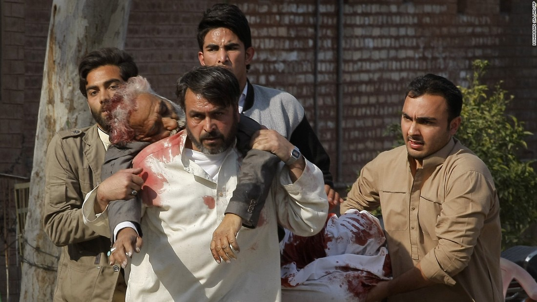 People rush an injured person to a hospital after the February 13 attack.