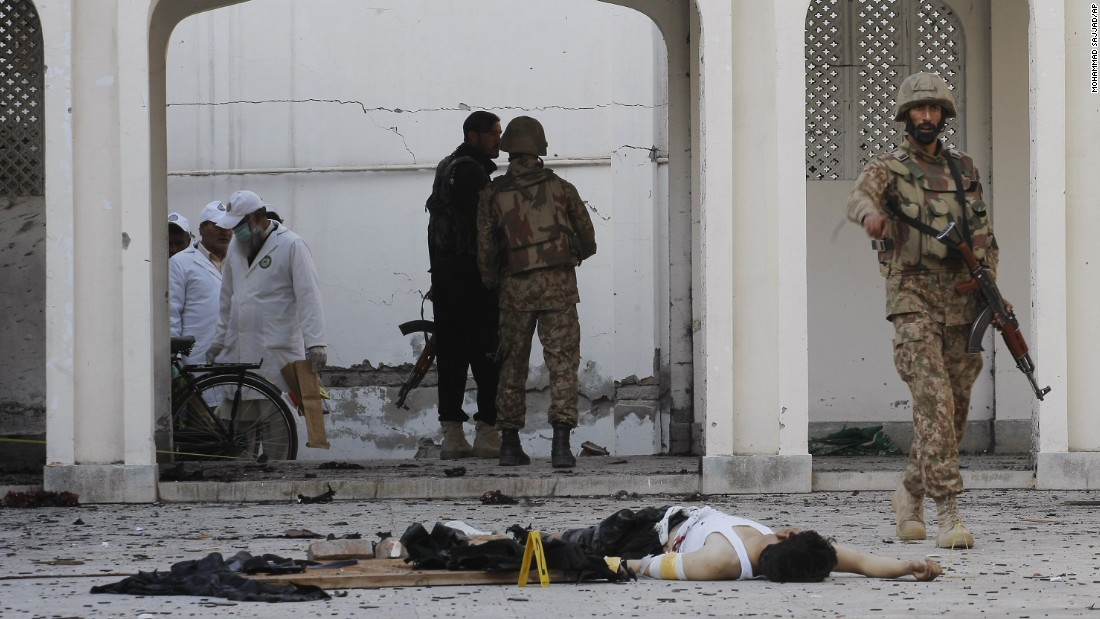 A soldier walks past the body of an attacker killed by security forces during the February 13 assault on the Shiite mosque.