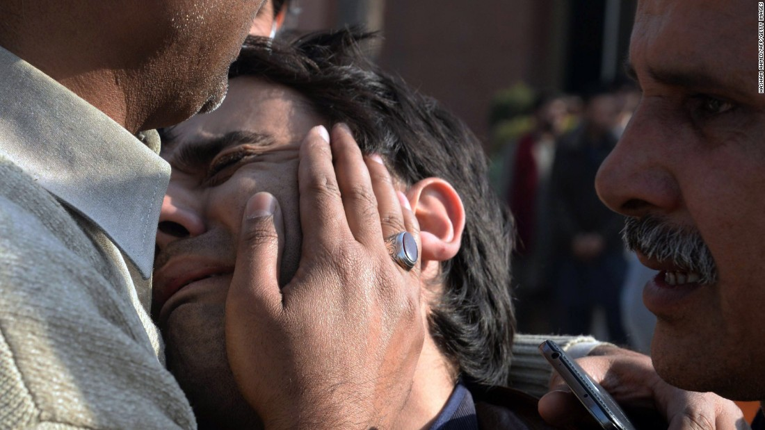 Relatives comfort a resident following the February 13 attack. The Islamist militant group said the attack was orchestrated by the mastermind of December's massacre at a Peshawar school that killed 145, including 132 children.