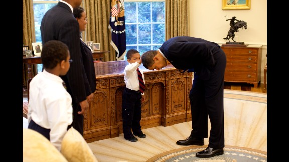Obama bends over so the son of a White House staff member can pat his head during a visit to the Oval Office in May 2009. The boy wanted to know if Obama