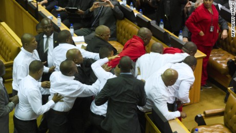 Members of the Economic Freedom Fighters, wearing red uniforms, are forcibly removed from parliament by security forces during South African President's State of the Nation address in Cape Town on February 12, 2015.