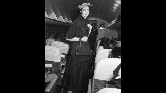 Dell'Orefice wore a hat and a mohair wrap while walking the aisle of an airplane during a 1955 fashion show.