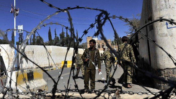 Houthi fighters guard the gate of the presidential palace where a bomb went off and wounded three people in Sanaa on Saturday, February 7.