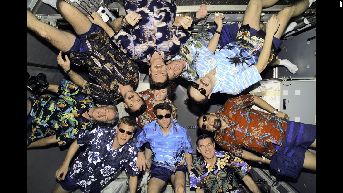 Astronauts aboard the International Space Station wear Hawaiian shirts for an April 2001 group portrait inside a space module.