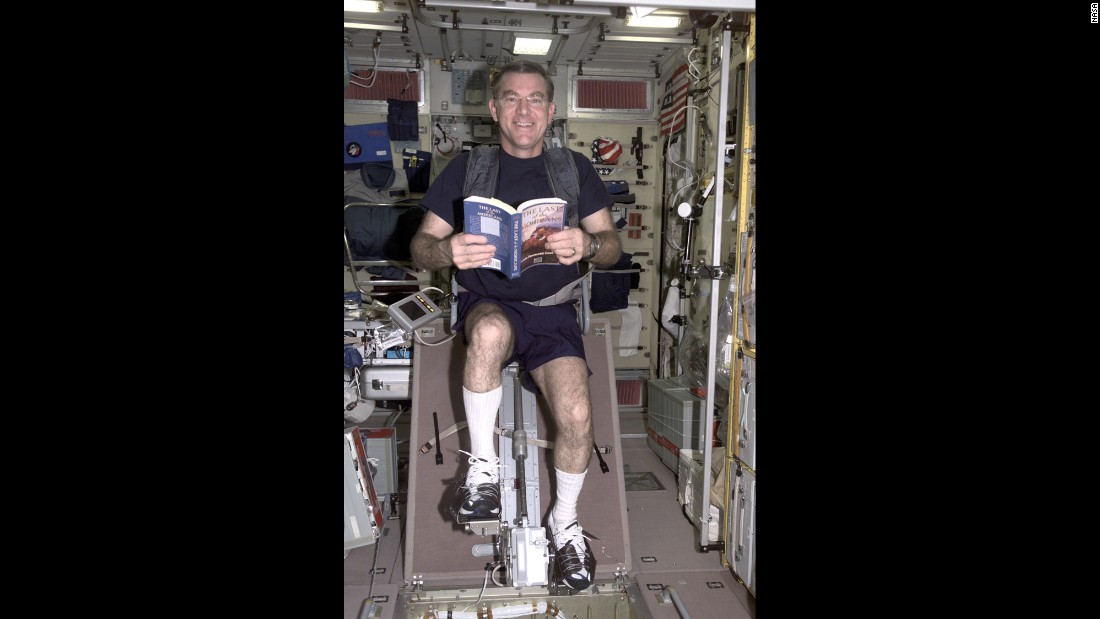"James S. Voss, Expedition Two flight engineer, reads the book ""The Last of the Mohicans"" while riding a stationary ergometer cycle aboard the International Space Station in 2001."