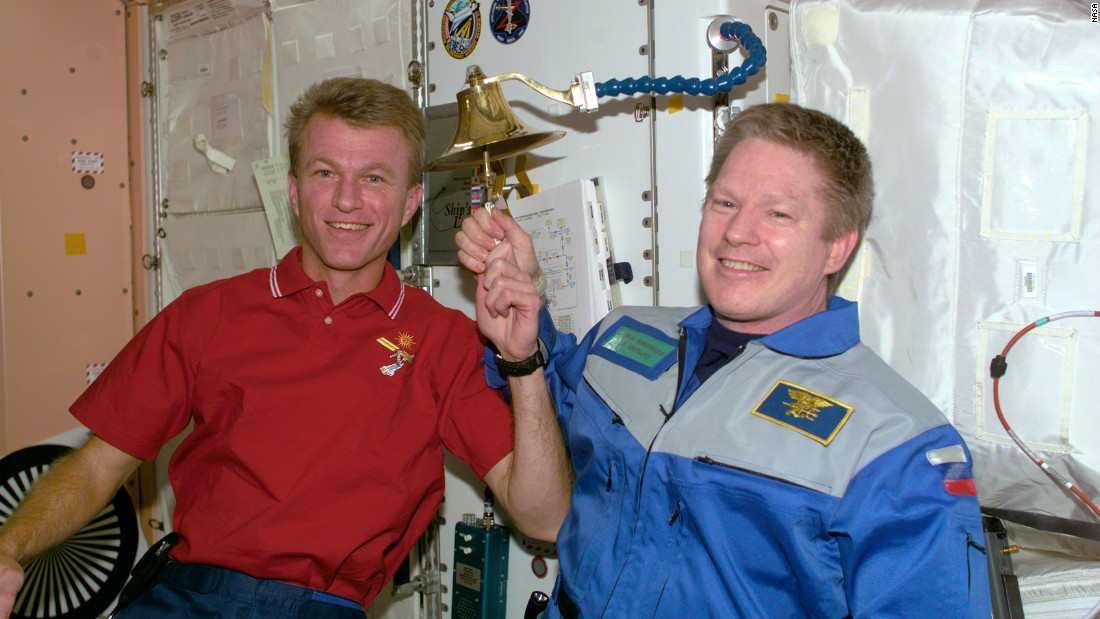 Astronauts Brent W. Jett, Jr., left, and William M. Shepherd observe an old Navy tradition of ringing a bell to announce the arrival of someone to a ship -- in this case, the International Space Station in 2000.