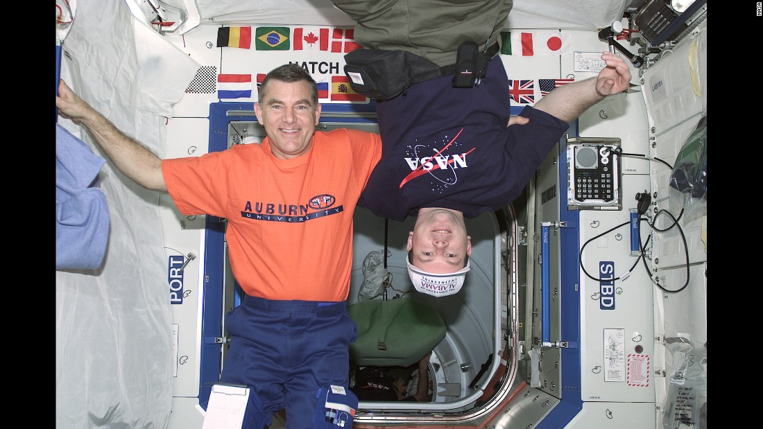In 2001 astronauts James S. Voss, left, and James M. Kelly share a friendly moment onboard the International Space Station's U.S. laboratory Destiny in spite of the longstanding rivalry between their respective alma maters, Auburn University and the University of Alabama.