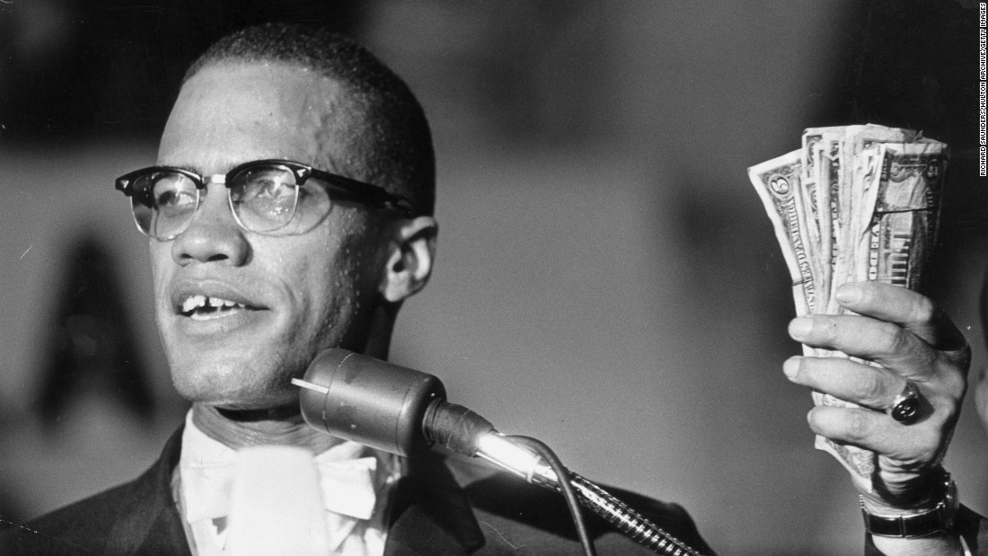 Malcolm X holds cash during a speech in Washington in 1963.