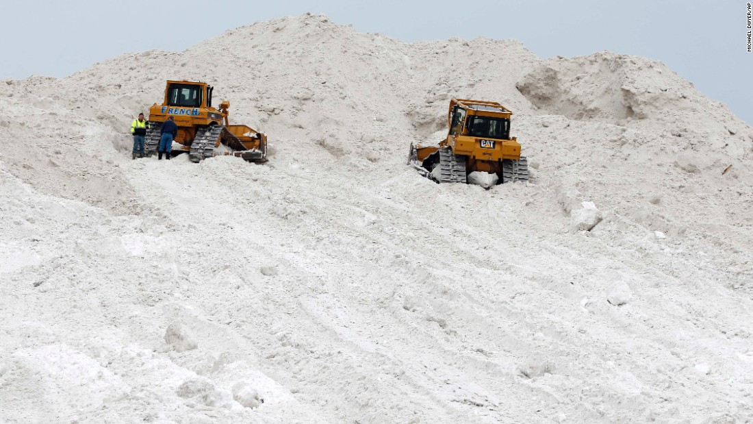 "A pair of bulldozers rest on a giant pile at a ""snow farm"" in Boston on February 14."