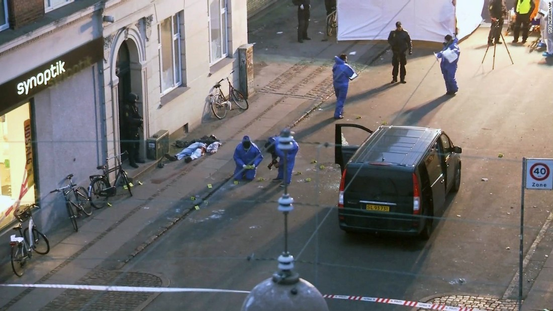 The body of a shooting suspect lies on the pavement, left, as Danish forensic officers examine the scene after police shot and killed the man early on February 15.