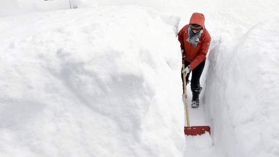 Kim Taylor of Norwood, Massachusetts, shovels a path in the snow in front of her home on February 15.
