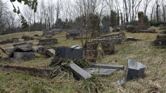 Several gray stone and glossy marble headstones are seen lying on the ground as if they had been toppled over.