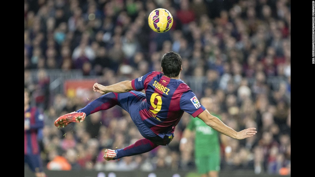 Barcelona striker Luis Suarez twists his body before volleying the ball into the net Sunday, February 15, during a Spanish league match against Levante. Barcelona won the match 5-0 and moved to within a point of league leaders Real Madrid.