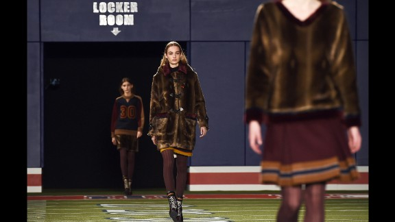 Models walk down a football stadium runway for Tommy Hilfiger's sporty fall collection.