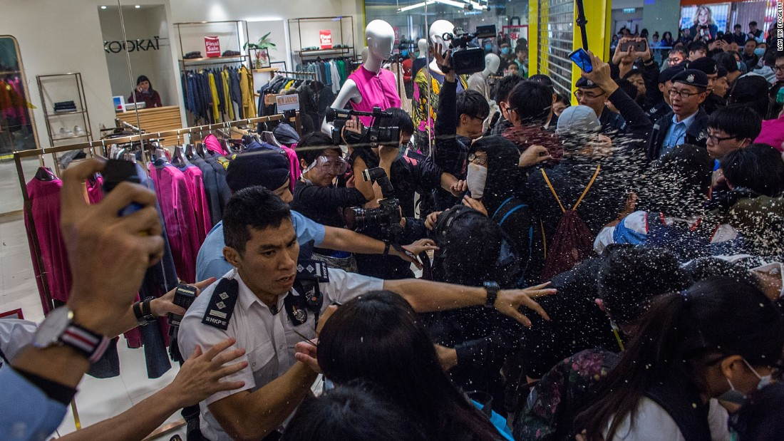 Police make arrests and use pepper spray against protesters in Hong Kong on February 15, as dozens of local residents rally against mainland Chinese shoppers in a popular shopping mall.