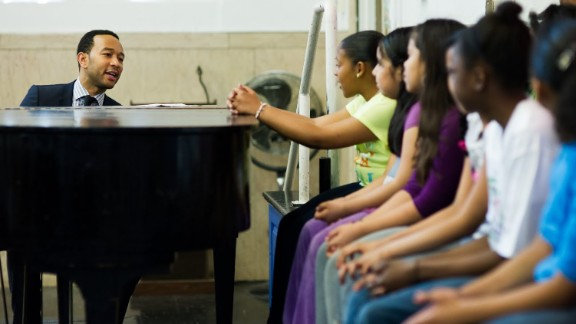 John Legend playing music with students