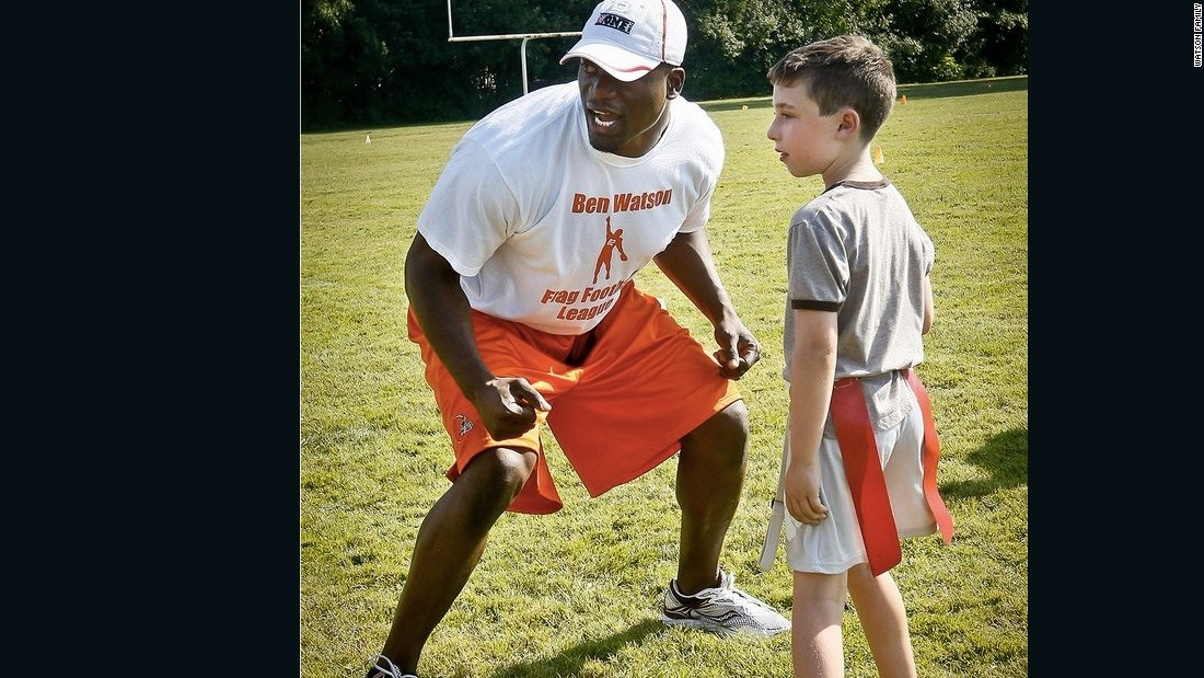 NFL Player Benjamin Watson works with child at One More Foundation's annual football clinic.