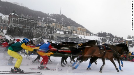 The ski resort of St Moritz acts as a backdrop as skijoring competitors set off for a race