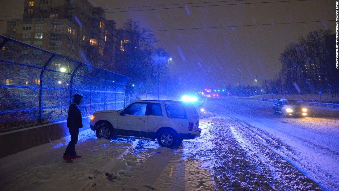 Daniyal Maveed waits to have his vehicle towed after sliding out of control in Reston, Virginia, on Monday, February 16.