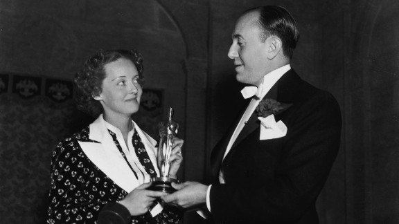 """<strong>Bette Davis (1936):</strong> Bette Davis and film producer Jack L. Warner hold Davis' best actress Oscar at the ceremony held in 1936. Davis won her first Oscar for her role in the film """"Dangerous."""""""