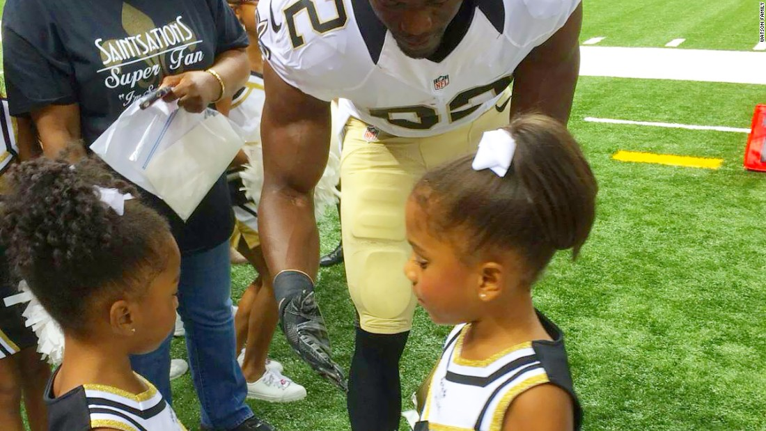 NFL Player Benjamin Watson on the field with his daughters Naomi (left) and Grace (right).