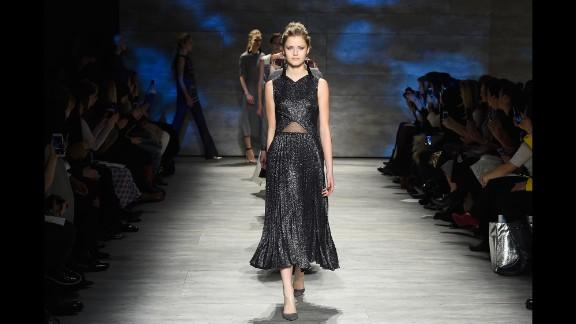 A model walks in a metallic pleated dress with tassel earrings for Lela Rose.