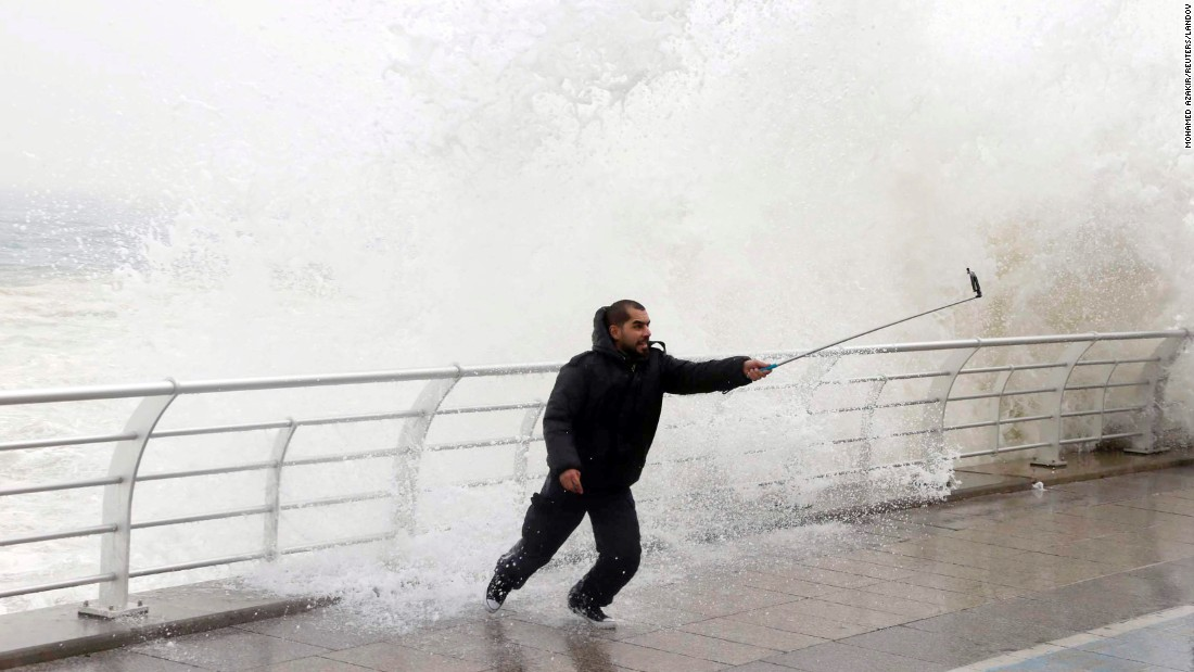 A man uses a selfie stick as a wave crashes behind him Wednesday, February 11, at a seaside promenade in Beirut, Lebanon.