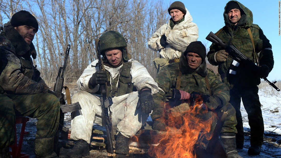 Pro-Russian rebels warm themselves by a fire during a break between fighting.