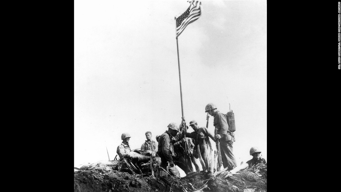 After the first flag-raising, Marines stand near Old Glory as it waves in the wind.