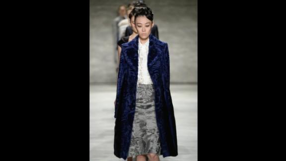 A model presents an indigo fur coat, tuxedo blouse and gray fur skirt for Bibhu Mohapatra.