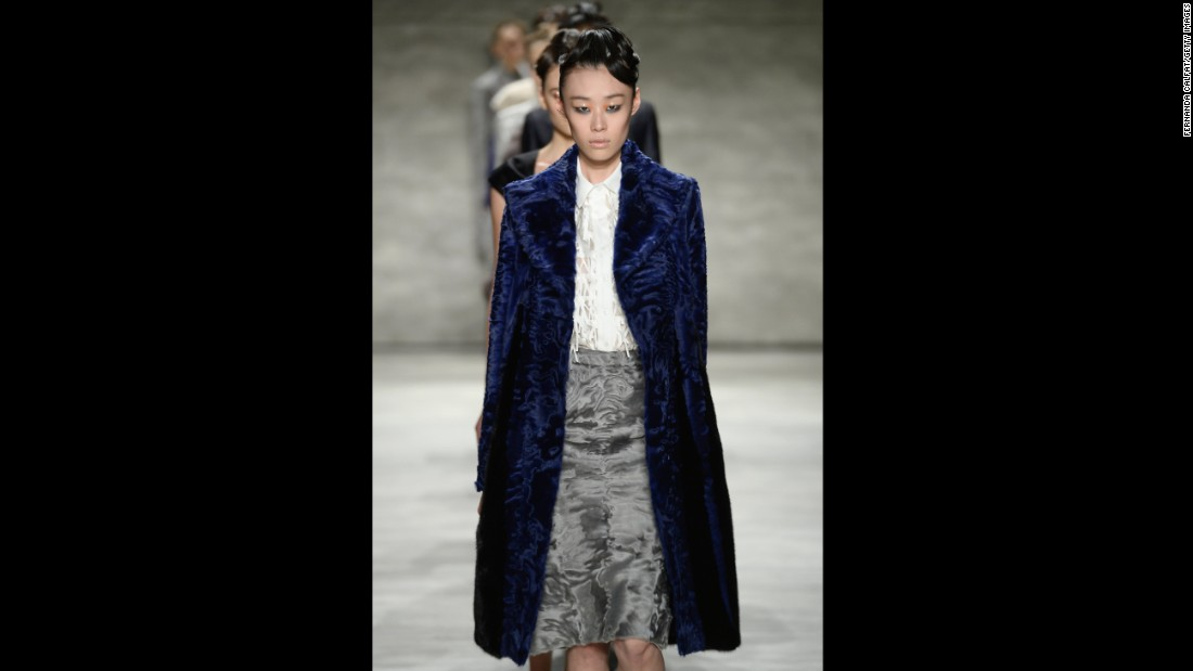 A model presents an indigo fur coat, tuxedo blouse and gray fur skirt for Bibhu Mohapatra.