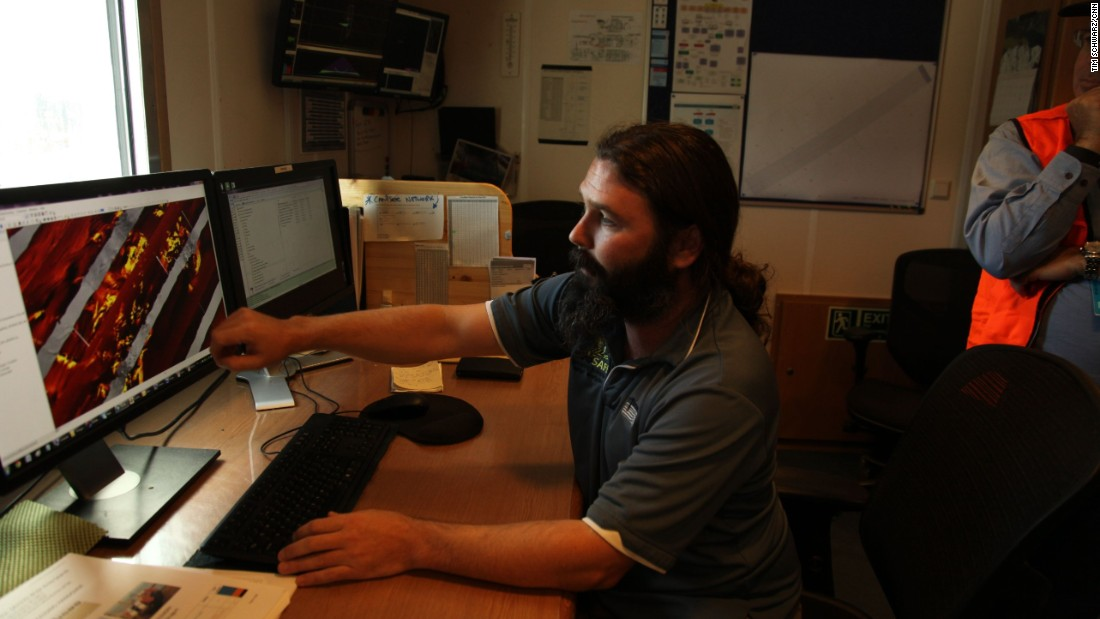 "Data supervisor James Kent explains how the side sensor tow fish drawn behind the ship systematically searches in the ocean floor with its side scan sonar towfish, ""flying"" four kilometers deep, only a hundred meters above the sea bed towed by the Discovery on the end of a ten kilometer long cable."