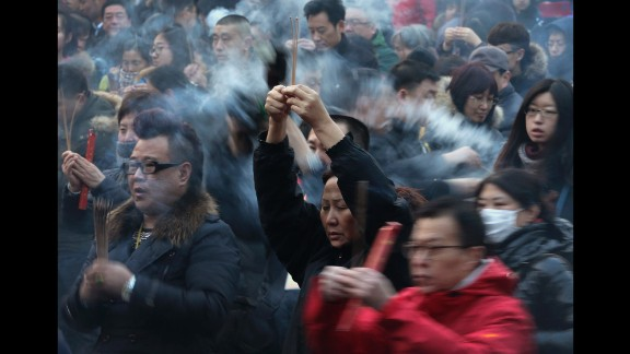 Worshipers burn incense while offering prayers at a temple in Beijing on February 19.