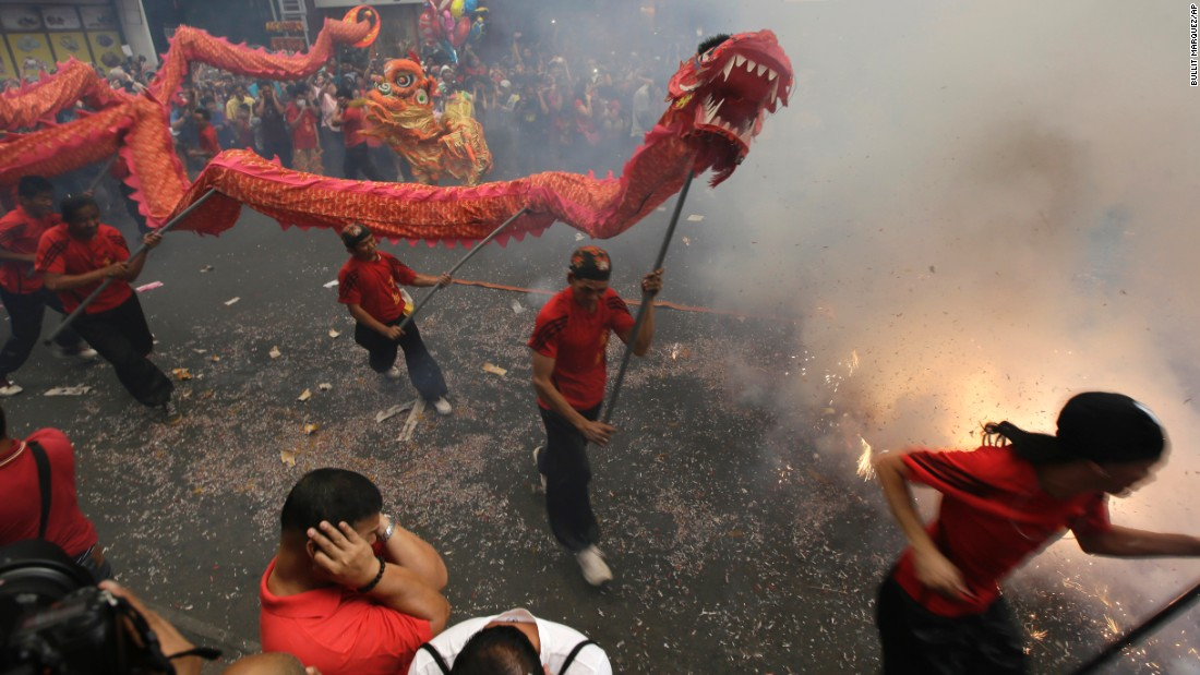 Firecrackers explode as dragon and lion dancers perform in front of a supermarket in Manila, Philippines, on February 19.