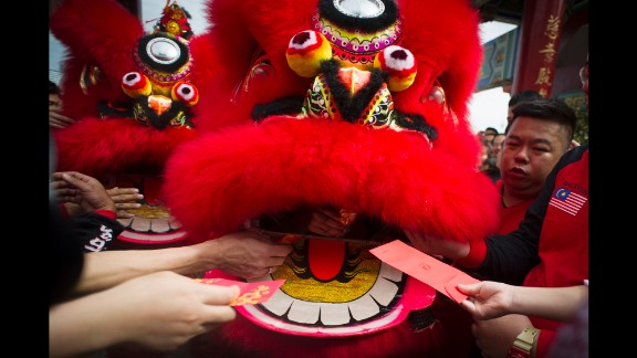 Temple visitors give red envelopes with money to a lion dance troupe during a performance in Kuala Lumpur, Malaysia, on February 19.
