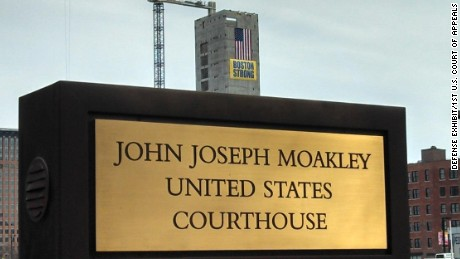 "Another ""Boston Strong"" banner rises above a sign for the federal courthouse in the city."