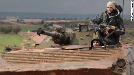 Rebel fighters drive a tank near the frontline in the village of Ratyan in the countryside north of the Syrian city of Aleppo on February 19, 2015. Fierce clashes are raging between rebel forces and government troops in the villages of Ratyan and Hardtaneen as regime forces cut the main rebel supply line into Aleppo. The Syrian regime is ready to suspend aerial bombardment of Aleppo to allow a humanitarian ceasefire, a UN envoy said, even as government troops sought to encircle embattled rebels. AFP PHOTO / ZEIN AL RIFAIZEIN AL-RIFAI/AFP/Getty Images
