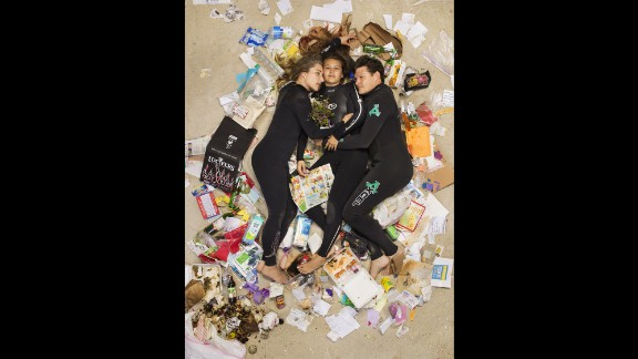 """Susan, Curtis and Brittany cuddled up on the beach in wetsuits in their """"7 Days of Garbage"""" shoot."""