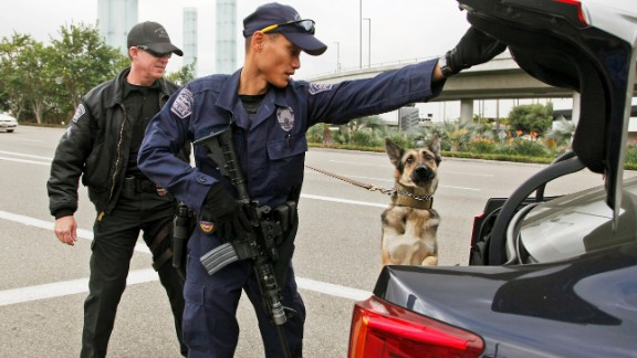 Officers inspect a car outside Los Angeles International Airport in 2013 after three TSA employees were shot.