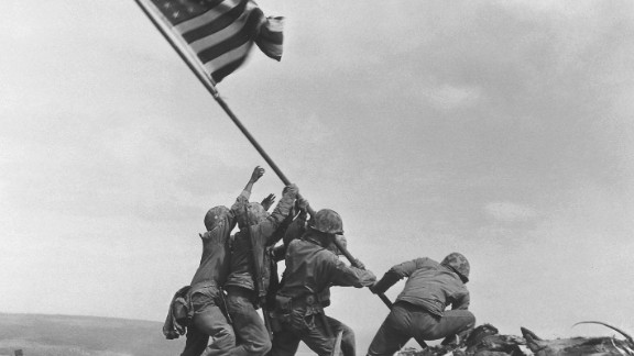 U.S. Marines raise a larger American flag hours later.