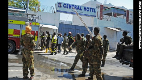 Somali security forces, medics and firefighters stand outside Mogadishu's Central Hotel after Friday's attack.