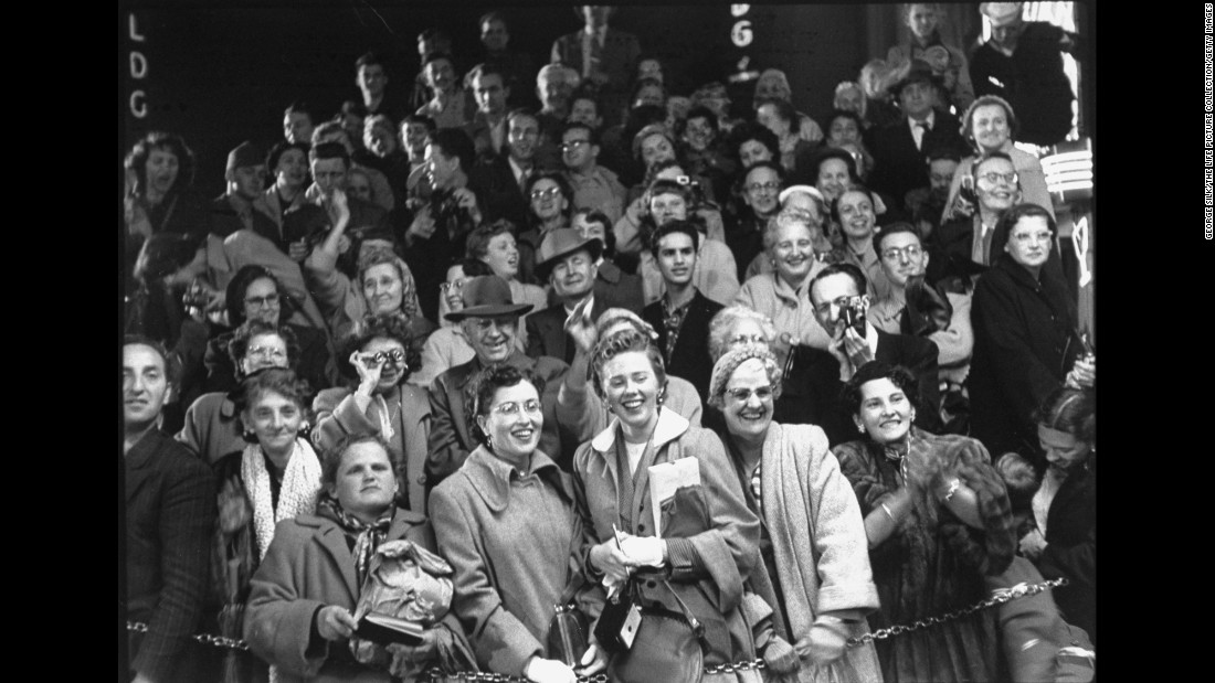 Crowd of fans watching as celebrities arrive at the RKO Pantages Theatre in 1954.