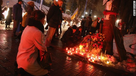 "KIEV, UKRAINE - FEBRUARY 20: Women kneel at a memorial to Nazar Voytovich, one of the many victims of the Maidan uprising one year ago, following an evening ceremony and concert of Mozart's ""Requiem"" attended by tens of thousands at Maidan square on February 20, 2015 in Kiev, Ukraine. Ukraine is commemorating the first anniversary of the February 20, 2014 sniper attacks that killed dozens of protesters on the Maidan and were followed by the ouster of Ukrainian President Viktor Yanukovich shortly later. Meanwhile fighting between pro-Ukrainian troops and pro-Russian separatists is continuing in the Donbas region of eastern Ukraine despite the recent Minsk ceasefire agreements. (Photo by Sean Gallup/Getty Images)"