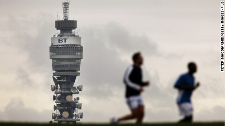 BT (British Telecom) Tower looms over two runners in Primrose Hill in London.