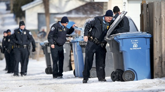Minneapolis police officers search garbage and recycling bins in an alley after a Minneapolis police officer was shot on Saturday, February 21 in Minneapolis.