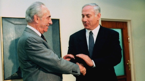 Netanyahu shakes hands with outgoing Israeli Prime Minister Shimon Peres before taking the office himself in June 1996.