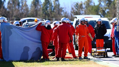 A screen is put up around Fernando Alonso's car as a medical team attends to the two-time world champion after his crash in testing.