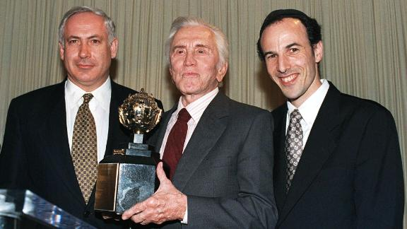 "Actor Kirk Douglas holds the King David Award, presented to him by the Jerusalem Fund of Aish HaTorah during a dinner in Beverly Hills, California, on November 17, 1997. Douglas was honored for his inspirational commitment to Israel and the Jewish people and in recognition of his new book ""Climbing the Mountain."" Netanyahu is on the left. To the right is Rabbi Nachum Braverman, director of the Jerusalem Fund of Aish HaTorah."