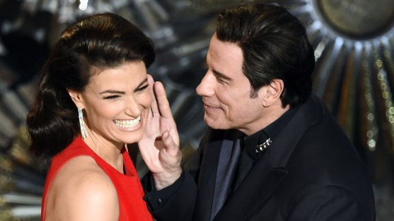 John Travolta and Idina Menzel present an award together, referencing last year's flub when he mispronounced her name.