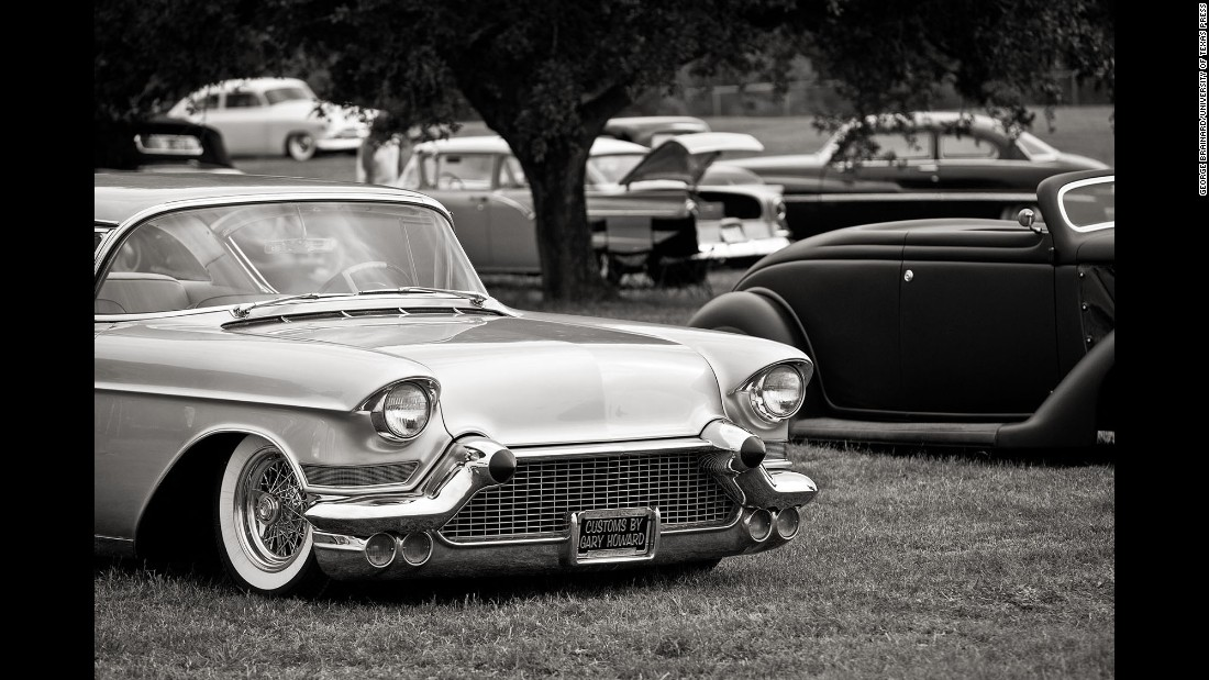 Various makes and models of classic cars are seen on the grounds of a show.